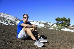 O homem senta-se na terra no pé da montanha nevado Foto de Stock