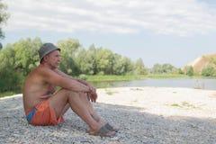O homem senta-se no banco do rio fotografia de stock