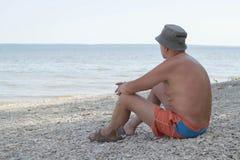 O homem senta-se no banco do rio foto de stock
