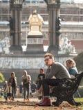 O homem senta-se no banco em Londres imagens de stock