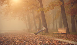 O homem senta-se no banco no parque um o dia nevoento fotografia de stock