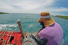 O homem senta-se no barco e em olhar o mar Fotos de Stock Royalty Free