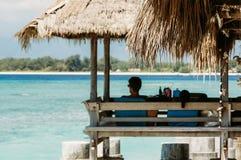O homem senta-se no miradouro da praia com folhas de palmeira imagem de stock royalty free