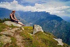 O homem senta-se no pico de montanha e olha-se para baixo no vale de Kullu Foto de Stock