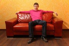o homem senta-se no sofá de couro vermelho Imagem de Stock Royalty Free