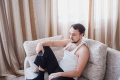 O homem senta-se no sofá na sala brilhante Imagens de Stock Royalty Free