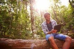 O homem senta-se no tronco de árvore em Forest Using Digital Tablet imagem de stock royalty free