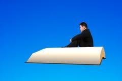 O homem senta-se no voo do livro no céu azul Foto de Stock Royalty Free