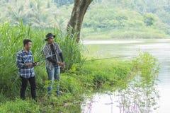 O homem senta-se nos peixes da pesca do riverbank fotos de stock