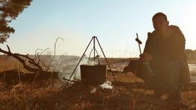 O homem senta-se para baixo pelo fogo e a parada engraçada do caminhante das quedas em fervuras de uma água do caminhante do acam vídeos de arquivo