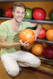 O homem senta-se perto das prateleiras com esferas e prende-se a esfera Imagem de Stock Royalty Free