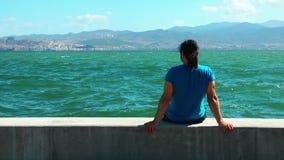 O homem senta-se perto do beira-mar filme