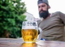 O homem senta o terra?o do caf? que aprecia cerveja defocused A cerveja do of?cio ? nova, urbana e elegante Cultura distinta da c fotografia de stock
