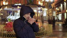 O homem sente o frio e funde o ar morno em suas mãos, tentativas para aquecer-se filme