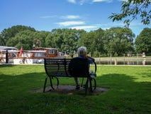 O homem sentou-se em um assento que admira os barcos no cais de Beccles no rio Waveney fotos de stock royalty free