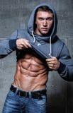 O homem 'sexy' novo muscular decola sua roupa Foto de Stock Royalty Free