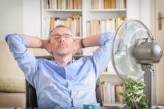 O homem sofre do calor no escritório ou em casa Foto de Stock