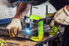 O homem solda uma máquina de soldadura do metal Imagem de Stock Royalty Free