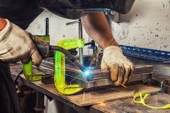 O homem solda uma máquina de soldadura do metal Imagens de Stock
