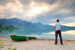 O homem sozinho senta-se no banco ao lado de um lago da montanha dos azuis celestes O homem relaxa Imagens de Stock