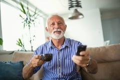 O homem superior aprecia olhar a tevê em casa foto de stock royalty free