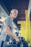 O homem superior ativo levanta peso no gym imagem de stock
