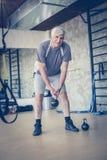 O homem superior ativo levanta peso no gym olhando a câmera fotos de stock royalty free