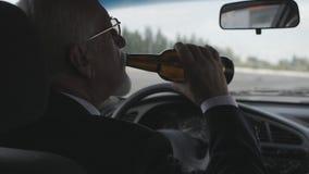 O homem superior bebe a cerveja ao sentar-se no carro Excitador bêbedo filme