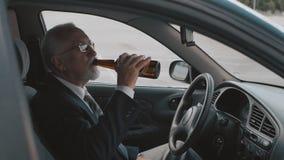 O homem superior bebe a cerveja ao sentar-se no carro Excitador bêbedo video estoque