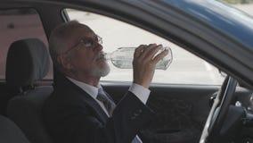 O homem superior bebe a vodca ao sentar-se no carro Excitador bêbedo video estoque