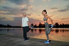 O homem superior e a moça que esticam os músculos aproximam o lago no por do sol fotografia de stock royalty free