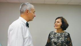 O homem superior e a mulher elegantes em uma data estão falando junto vídeos de arquivo