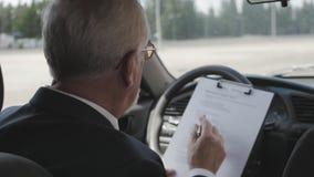 O homem superior está estudando originais ao sentar-se no carro Homem de negócios ocupado filme