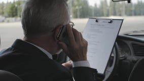O homem superior está estudando os originais e está falando no telefone ao sentar-se no carro Homem de negócios ocupado filme