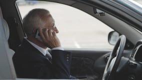 O homem superior está falando no telefone celular no carro video estoque