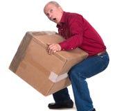 O homem superior leva uma caixa pesada Fotografia de Stock Royalty Free