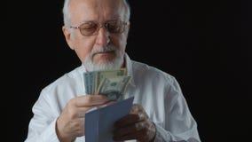 O homem superior obtém o envelope com dinheiro Conta notas de dólar Conceito do salário filme