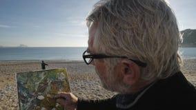 O homem superior pinta uma imagem na praia O artista masculino idoso faz os toques finais com a espátula no moderno vídeos de arquivo