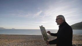 O homem superior pinta uma imagem na praia O artista masculino idoso faz os toques finais no sumário moderno vídeos de arquivo