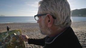 O homem superior pinta uma imagem na praia O artista masculino idoso faz toques finais rápidos com a espátula no moderno vídeos de arquivo