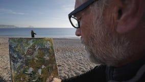 O homem superior pinta uma imagem na praia O artista masculino idoso faz toques finais rápidos com a espátula no moderno video estoque