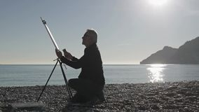 O homem superior pinta uma imagem na praia Artista masculino idoso que pinta a lona na armação do metal na praia contra