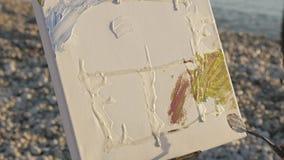 O homem superior pinta uma imagem na praia Close-up disparado do artista masculino idoso que pinta a lona com uma espátula em filme