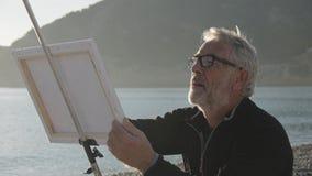 O homem superior pinta uma imagem na praia Tiro meados de do artista masculino idoso que pinta a lona na praia do mar no por do s