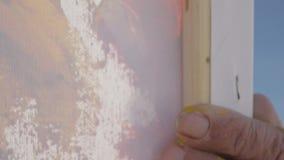 O homem superior pinta uma imagem Tiro extremo do close-up de pintar a lona com uma espátula larga Vista traseira Movimento lento filme