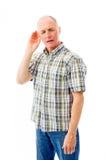 O homem superior que tenta escutar isolou-se no fundo branco Fotografia de Stock Royalty Free