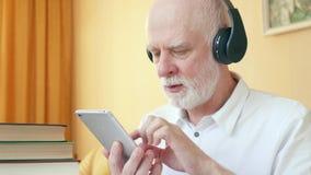 O homem superior usa a aplicação para o treinamento de habilidades de escuta, aprendendo a língua estrangeira no smartphone vídeos de arquivo