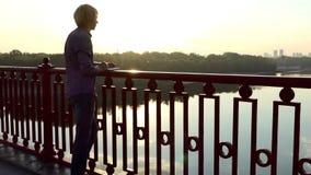 O homem talentoso golpeia ideias e põe-nas para baixo em um bloco de notas sobre uma ponte filme