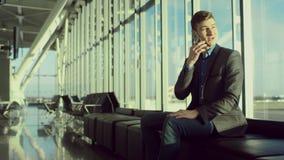 O homem tallking sobre seu smartphone ao sentar-se no aeroporto video estoque
