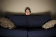 O homem amedrontado espreita sobre um sofá ao olhar a tevê Fotografia de Stock